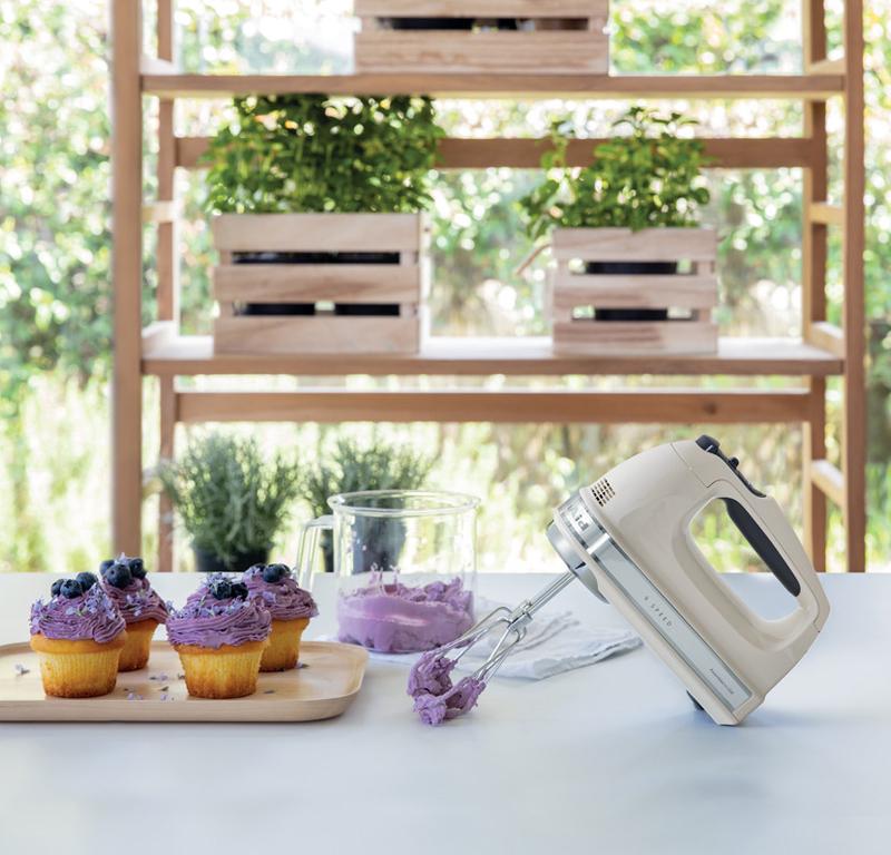 Cream hand mixer and purple cupcake