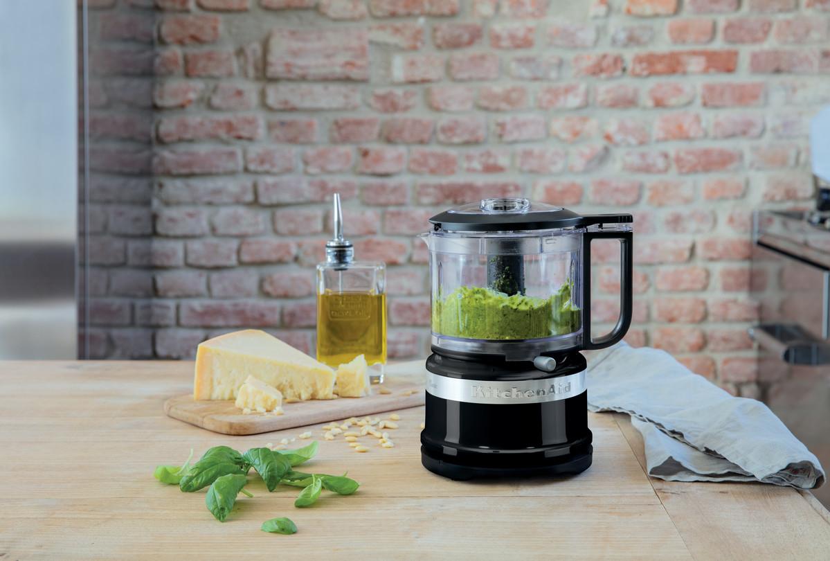 Black mini food chopper preparing green pesto