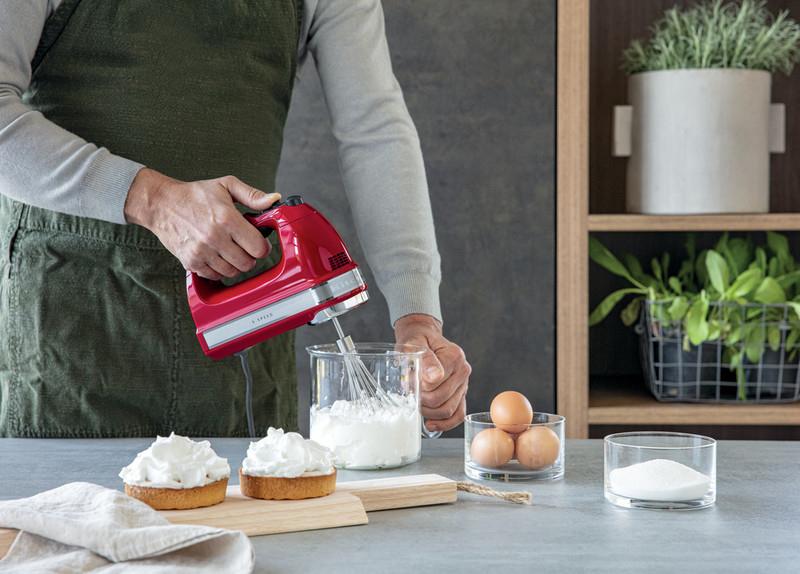 Red hand mixer beating egg whites for lemon meringue pie