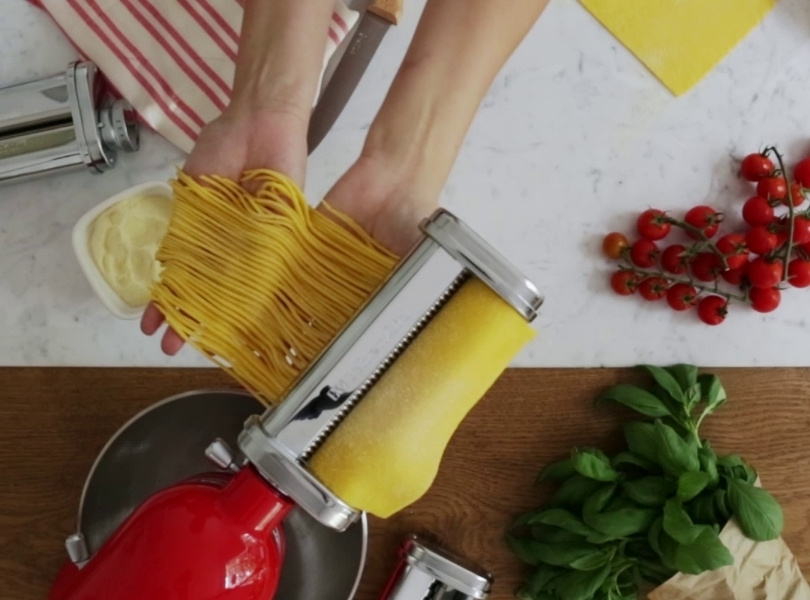 Red stand mixer making linguini with pasta cutter