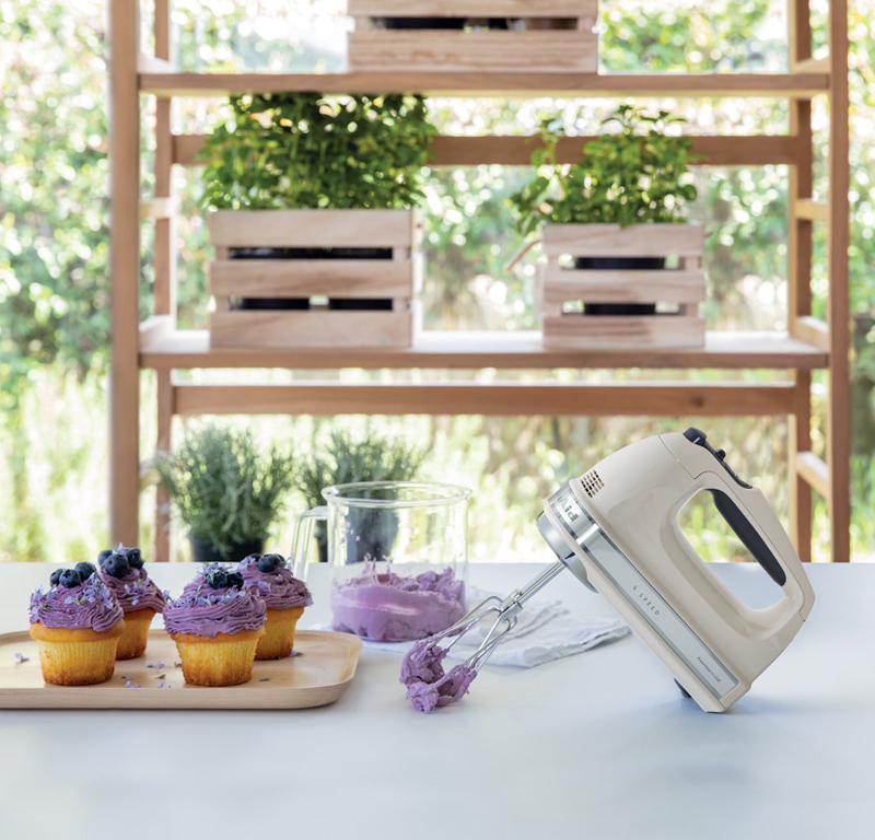 Cream hand mixer and purple cupcake