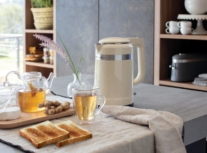 Cream kettle design and cup of ginger tea