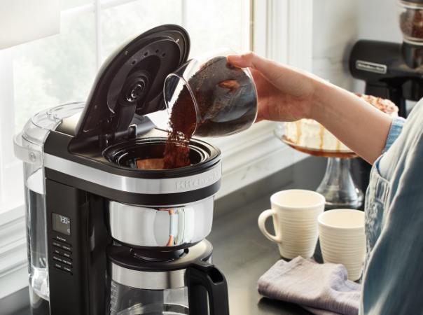 Adding coffee in black filter coffee machine