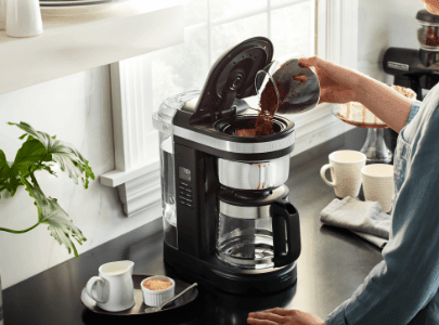 Black drip coffee maker being filled with coffee