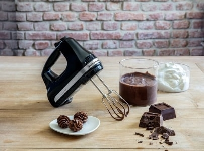 Black hand mixer making chocolate bites