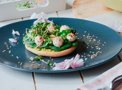 Bagel with rucola on blue plate