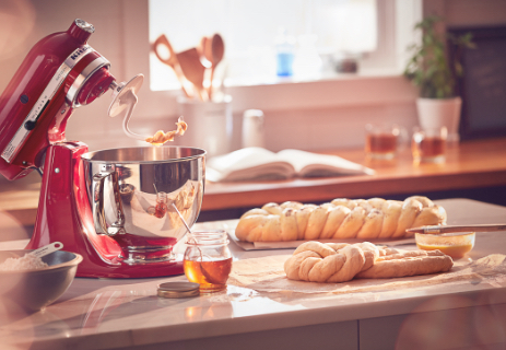 Red mixer and dough hook with fresh bread made