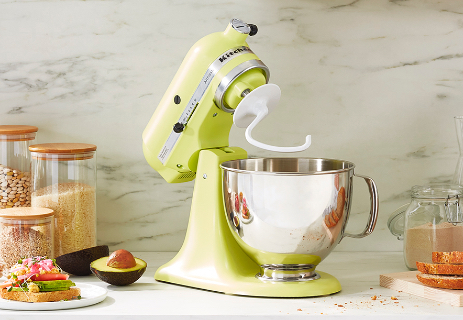 Dough hook on yellow mixer with stainless steel mixing bowl