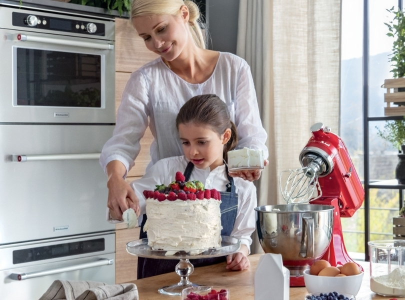 Mom and daughter making cake with red fruits with red mixer