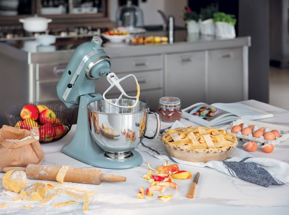 Blue mixer preparing apple pie using a paddle attachment
