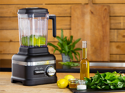 Black blender preparing green sauce