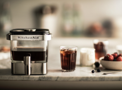 Cold brew coffee maker with glass of ice coffee