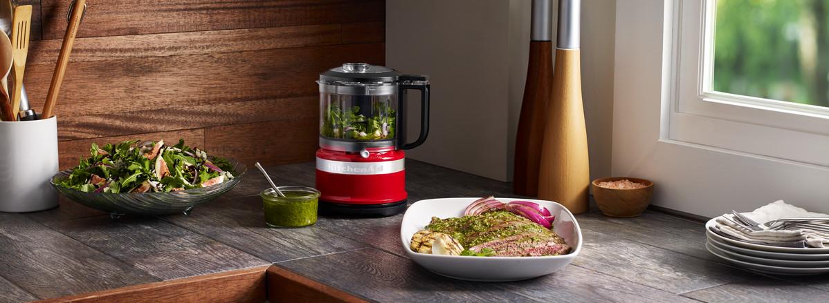 Red mini food chopper preparing green marinade