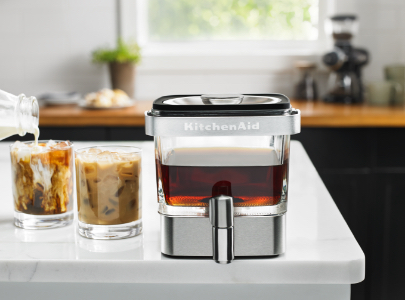 Cold brew coffee maker and glasses of ice coffee with milk