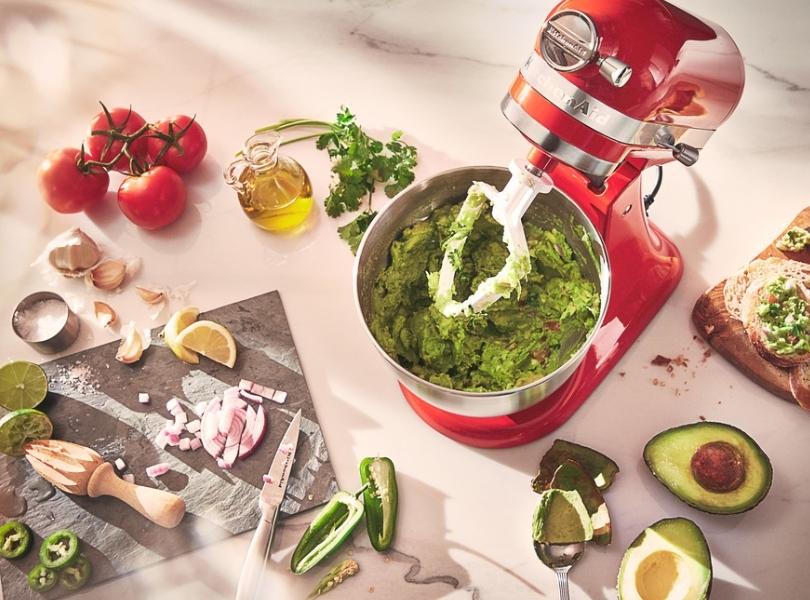 Red mixer preparing guacamole using a flat beater
