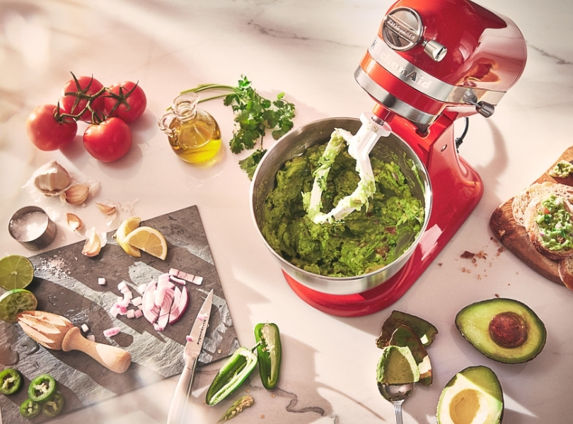 Red mixer preparing guacamole using a flat beater