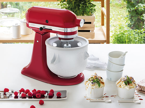 Ice cream maker on red mixer with vanilla ice cream and raspberries