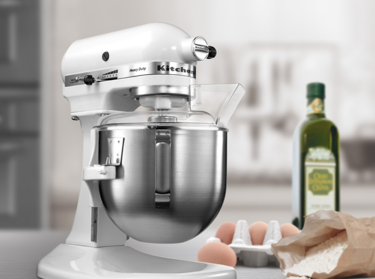 White mixer preparing dough with eggs and flour