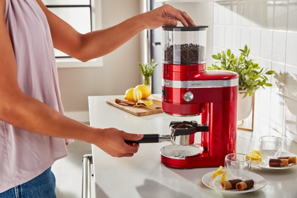 Women grinding coffee beans in red Artisan grinder