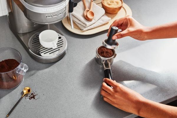 tamp coffee near grey espresso machine